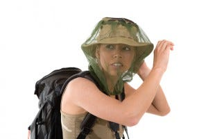 blond girl hiding her face behind a mosquito net that goes over her hat